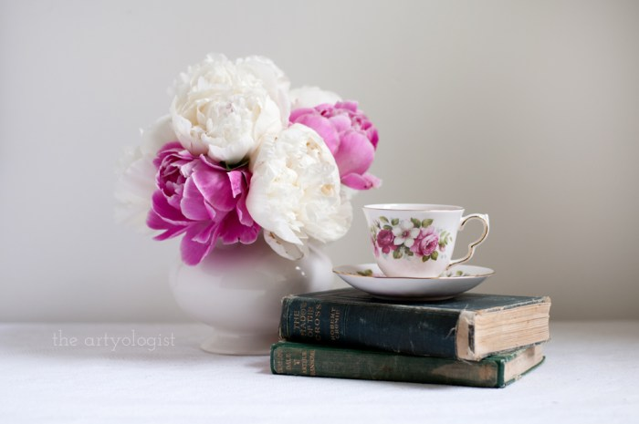 a bouquet of pink and white flowers, and a teacup atop a stack of books