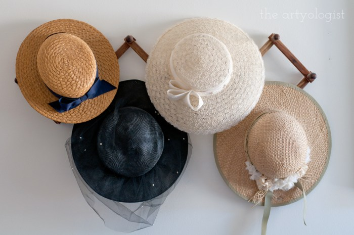 straw hats hanging on a peg rack
