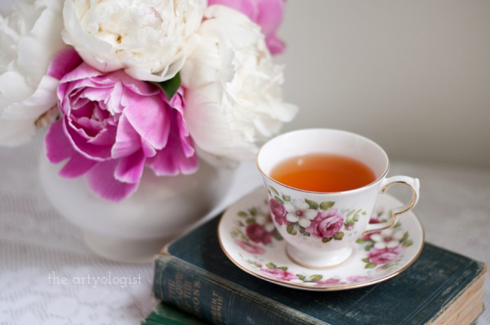 a china teacup with a bouquet of pink and white peonies