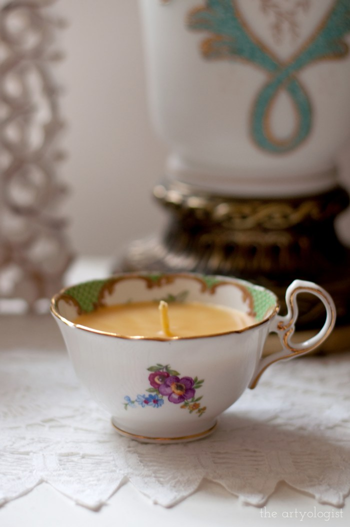 a candle in a pretty floral teacup, sitting on a nightstand