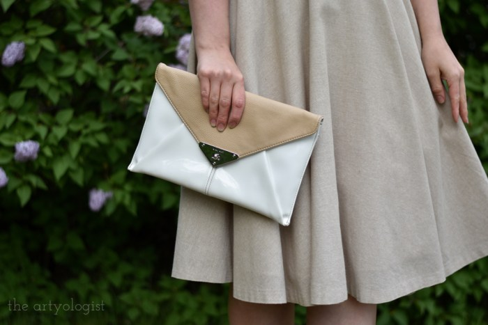 holding an envelope style white and tanclutch