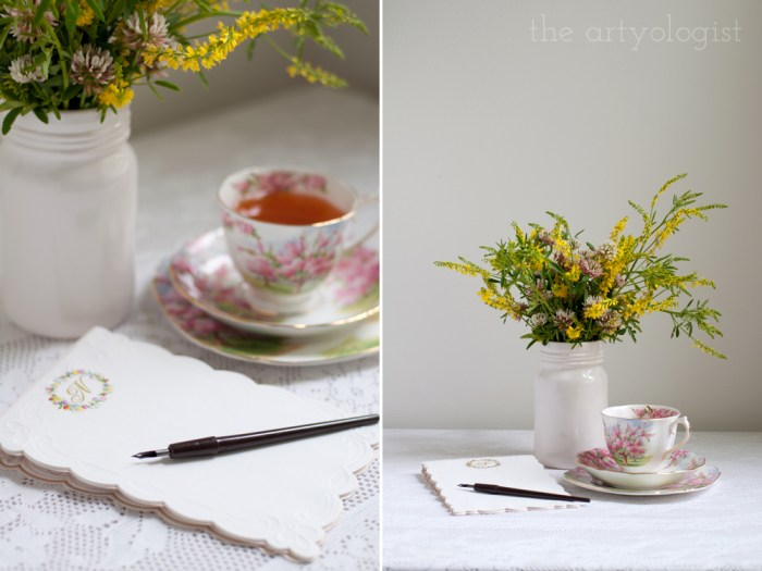 writing a letter at a desk with a cup of tea and a bouquet of flowers