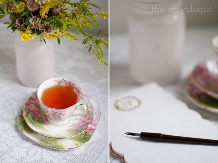 a paper pad with a nib pen on top of it and a cup of tea beside it