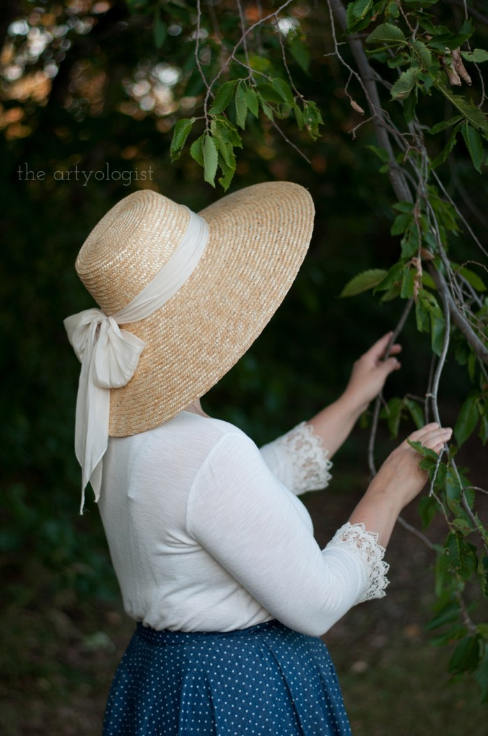 woman wearing a straw hat with a silk bow on it