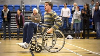 A screencap from Siblings episode 'Wheelchair Conference', with ble-bodied Tom Stourton playing able-bodied Dan who is pretending to be disabled.