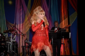 Charo performing in front of TheatreWorld's Professional Le Cirque Celebration Backdrop