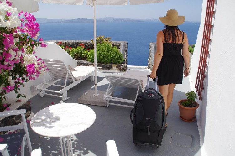 Girl in Santorini with Osprey Meridian Luggage
