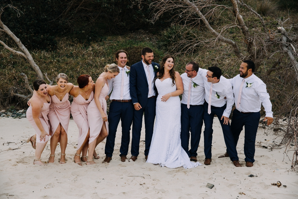 Bridal party laughing on beach