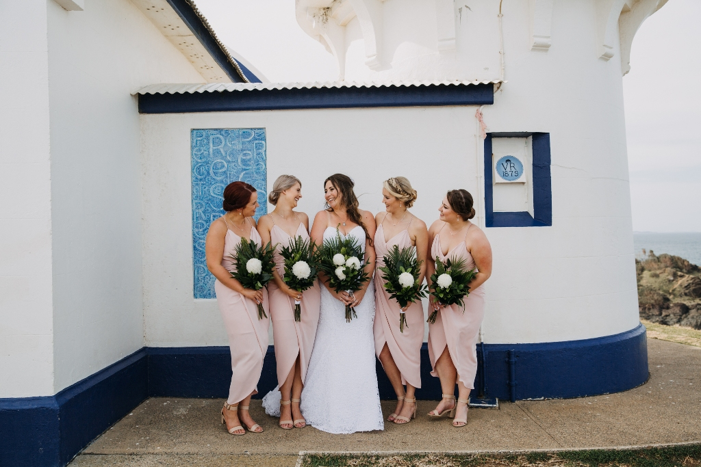 Bride and Bridesmaids laughing in front of Lighthouse