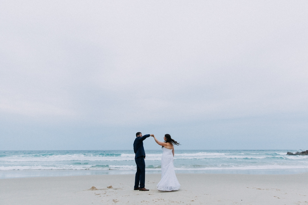 Bride and Groom dancing on beach at dusk