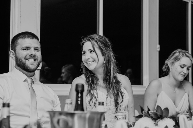 Bride and Groom smiling through speeches