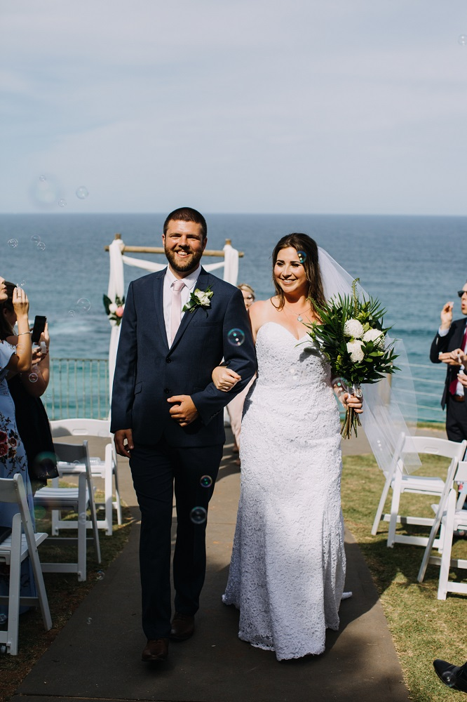 Couple walking down aisle with bubbles
