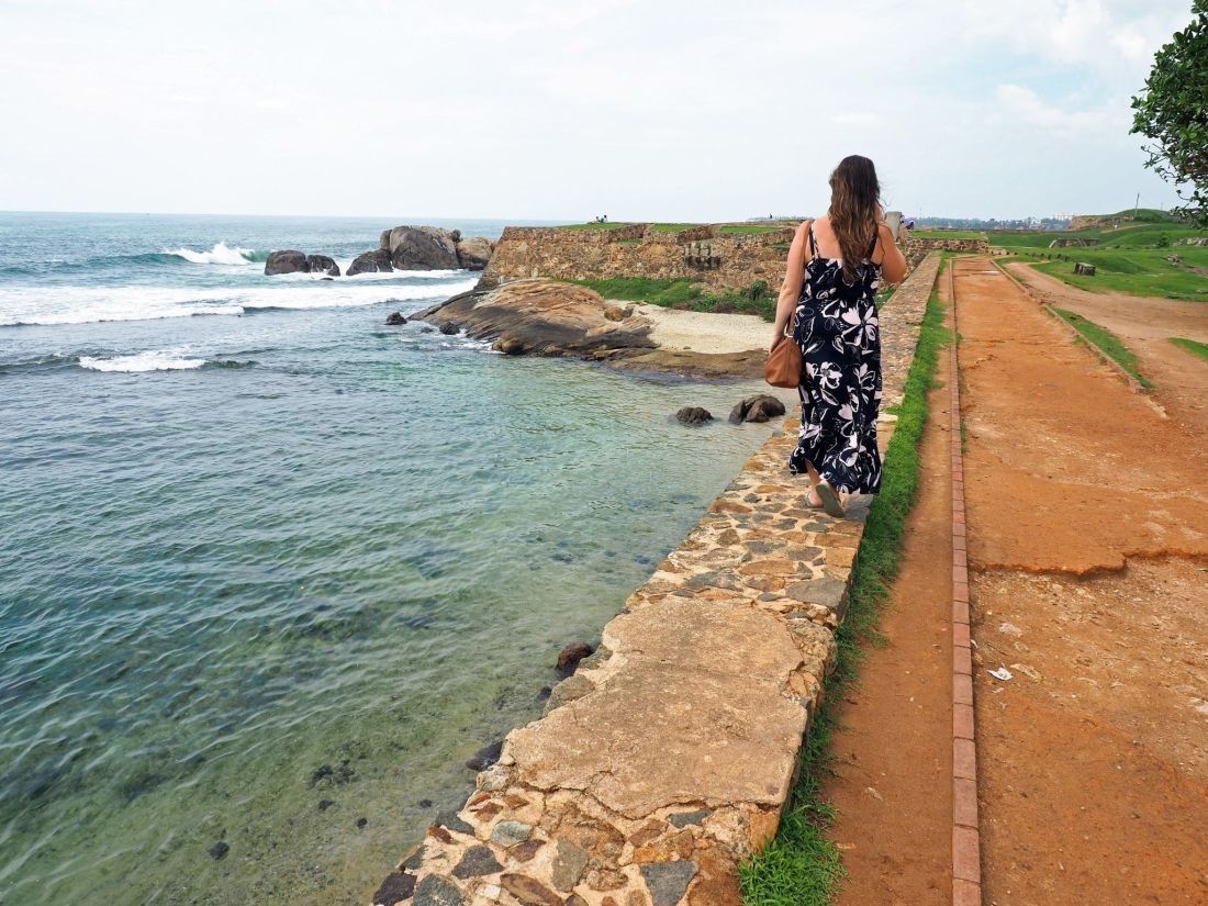 Girl walking fort walls in Galle