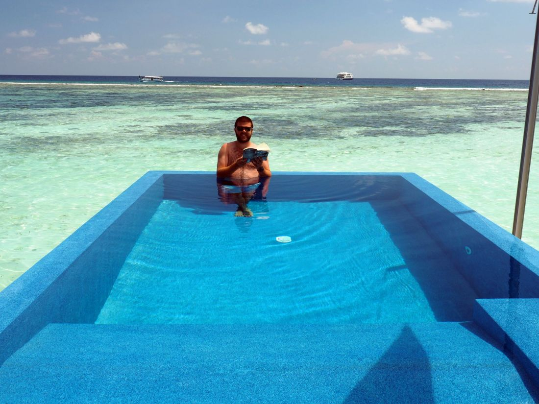 Dan reading book in Overwater Bungalow Infinity Pool LUX Maldives