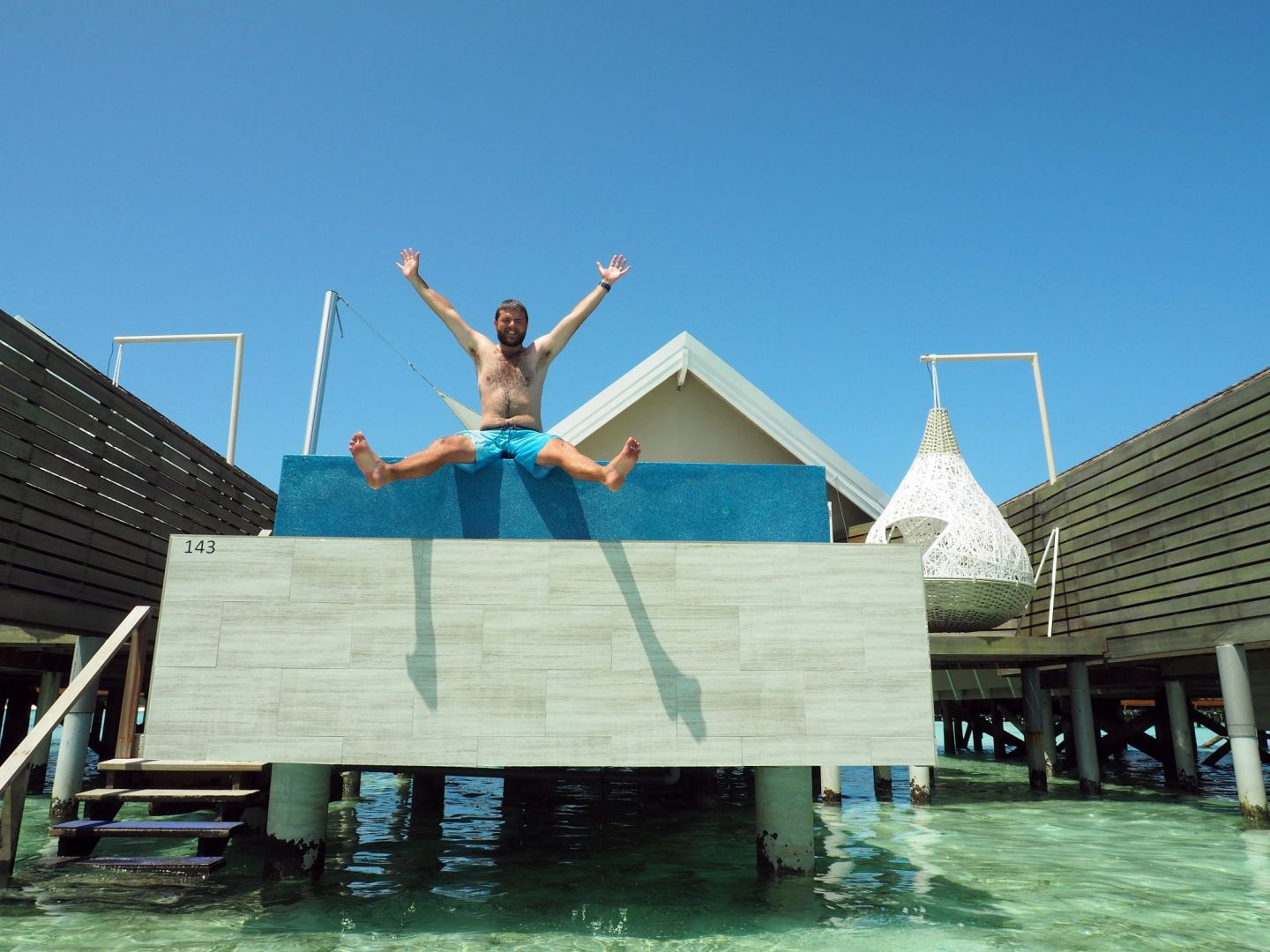 Dan sitting on edge of Overwater Bungalow Infinity Pool LUX Maldives