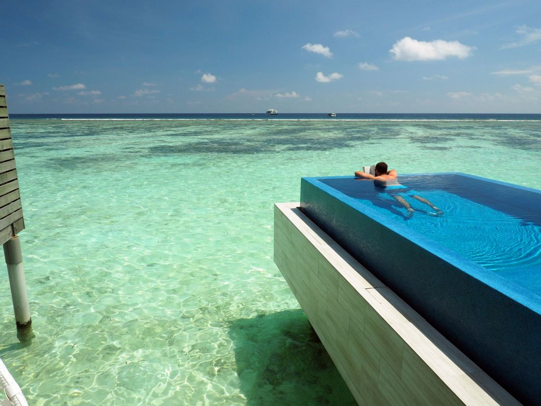 Reading book in Overwater Bungalow Infinity Pool LUX Maldives