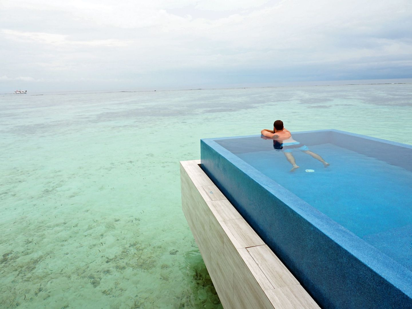 Swimming in infinity pool LUX Maldives