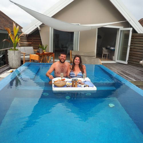 Couple enjoying floating Breakfast in villa at LUX South Ari Atoll
