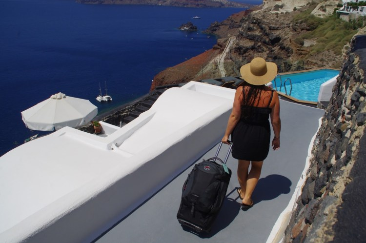 Girl with suitcase in Santorini