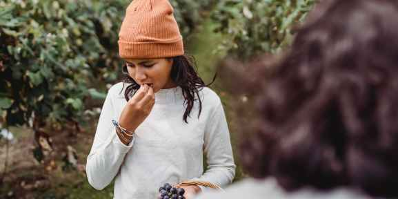 ethnic girl trying delicious grapes in garden