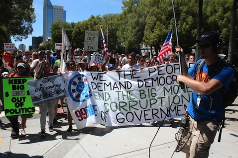 "Marchers say, ""We the people demand Democracy. End the Big Money corruption of government."" Photo by Dan Bacher."