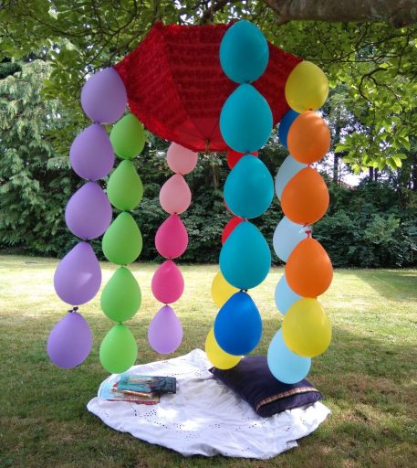 umbrella hanging in a tree with colourful compostable balloons trailing from it