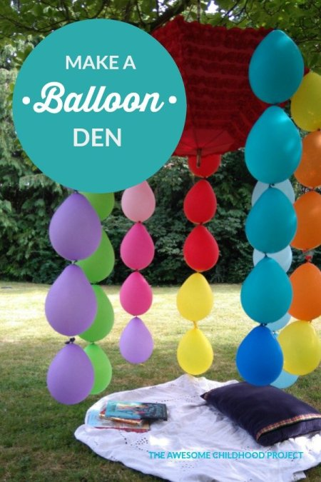 compostable balloons trailing from an upside down umbrella in a tree for a garden party