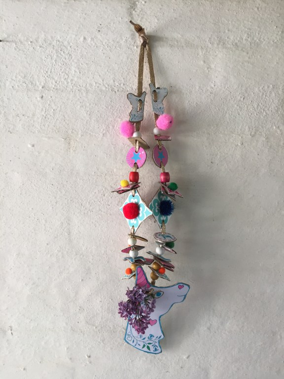 a pretty kids unicorn cardboard junk necklace with flowers, pompoms and sequins made with a free childrens craft printable