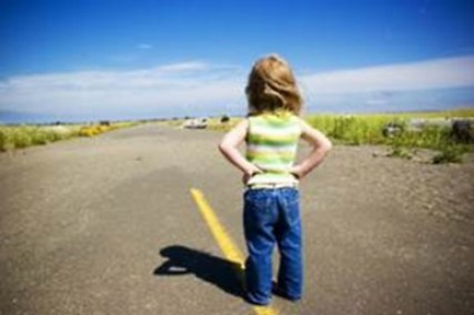little girl looking down highway