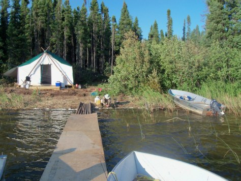 A fisherman performs some camp chores at a lake outpost camp on a fishing trip to silsby lake lodge in northern manitoba canada