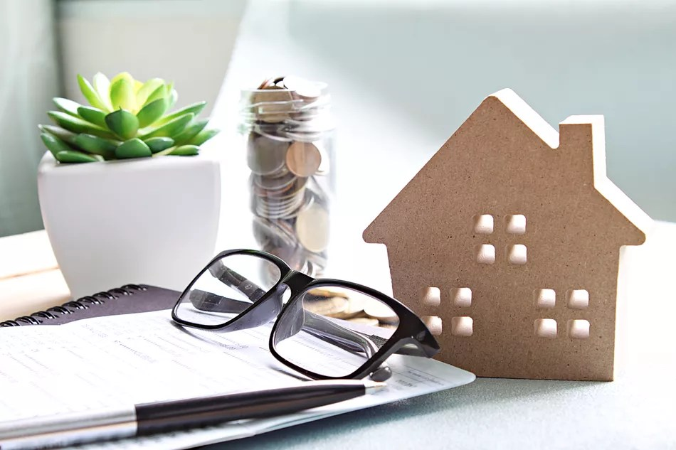 Wood house model, coins, eyeglasses and saving account book or financial statement on office desk table