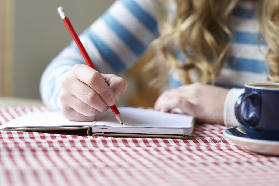 Woman writing in notepad, close up.