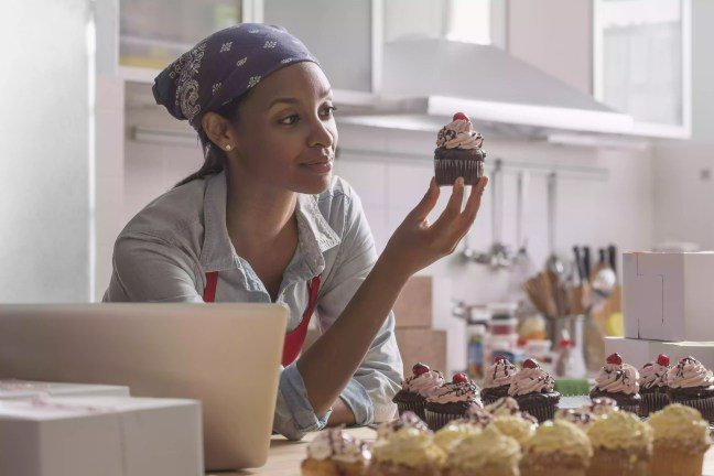 Mixed race baker admiring cupcake in commercial kitchen