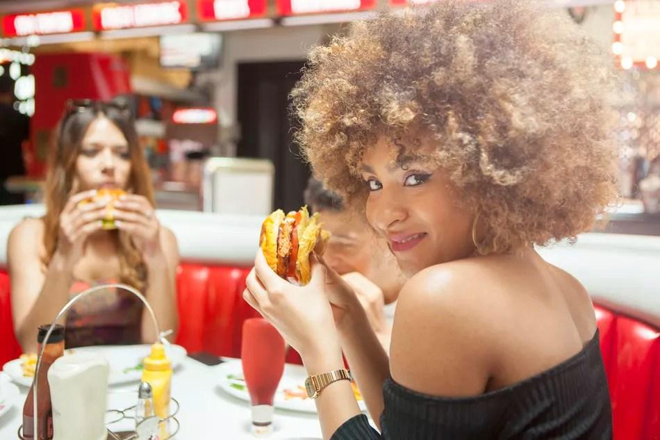 Женщины едят фаст-фуд
