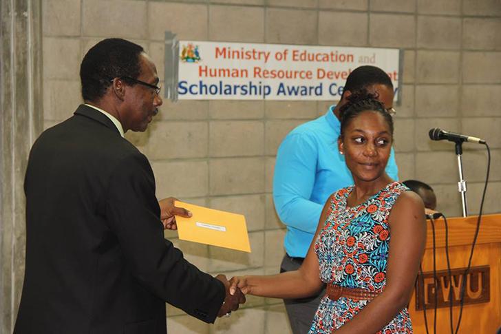 Minister Boatswain presents Leshae Cenac with scholarship award