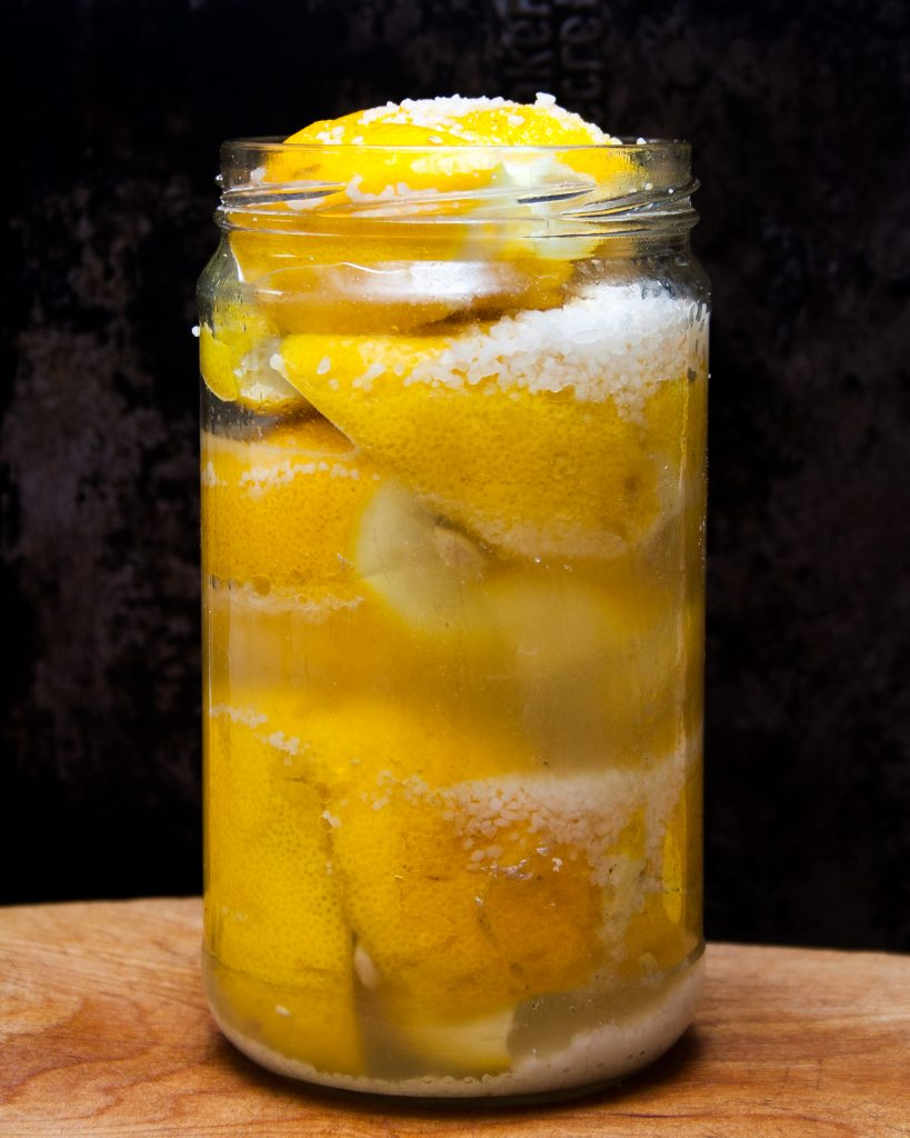A photo of lemons and salt packed into a jar.