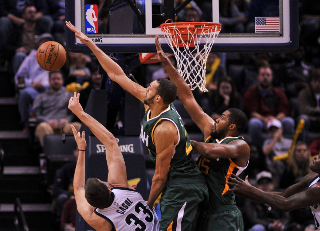 Dec 18, 2016; Memphis, TN, USA; Memphis Grizzlies center Marc Gasol (33) shoots against Utah Jazz center Rudy Gobert (27) and Utah Jazz forward Derrick Favors (15) during the second half at FedExForum. the Utah Jazz defeat the Memphis Grizzlies 82-73. Mandatory Credit: Justin Ford-USA TODAY Sports