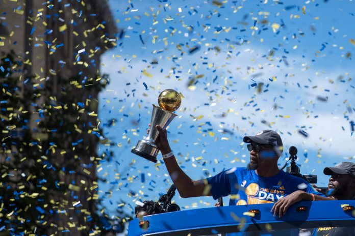 June 15, 2017; Oakland, CA, USA; Golden State Warriors forward Kevin Durant (35) hoists the MVP trophy during the Warriors 2017 championship victory parade in downtown Oakland. Mandatory Credit: Kyle Terada-USA TODAY Sports
