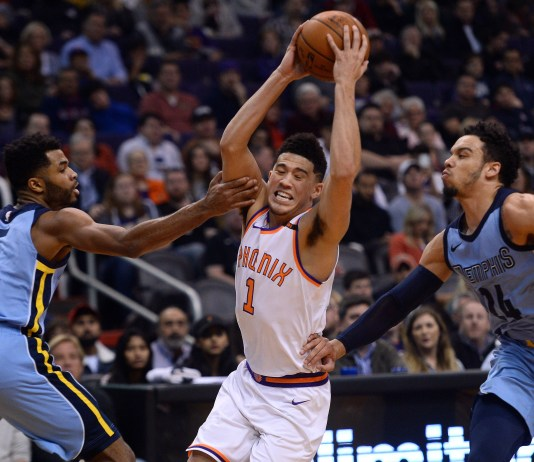 Dec 26, 2017; Phoenix, AZ, USA; Phoenix Suns guard Devin Booker (1) drives by Memphis Grizzlies guard Andrew Harrison (5) and Memphis Grizzlies forward Dillon Brooks (24) during the first half at Talking Stick Resort Arena. Mandatory Credit: Joe Camporeale-USA TODAY Sports