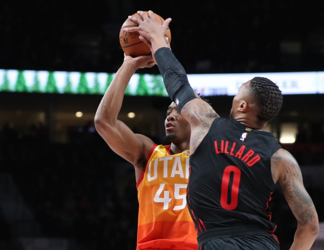 Feb 11, 2018; Portland, OR, USA; Portland Trail Blazers guard Damian Lillard (0) blocks the shot from Utah Jazz guard Donovan Mitchell (45) in the second half at Moda Center. Mandatory Credit: Jaime Valdez-USA TODAY Sports