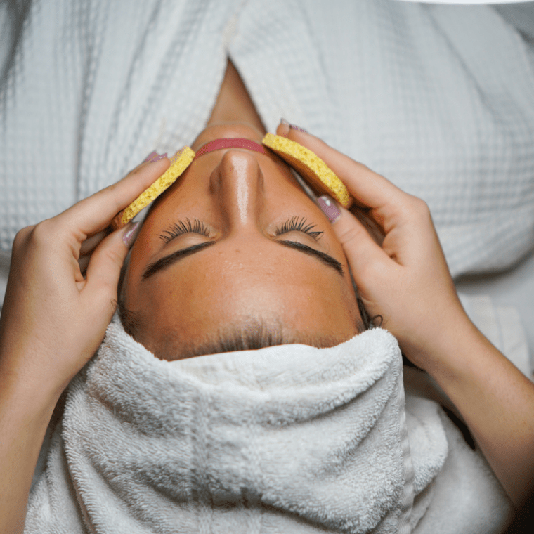 a women getting her face washed with sponges as she lays on the spa table