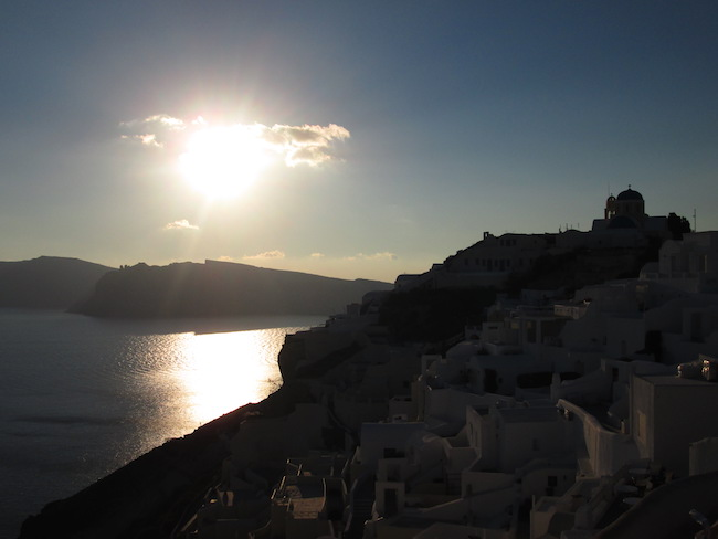 The sun creeping toward the ocean in Oia