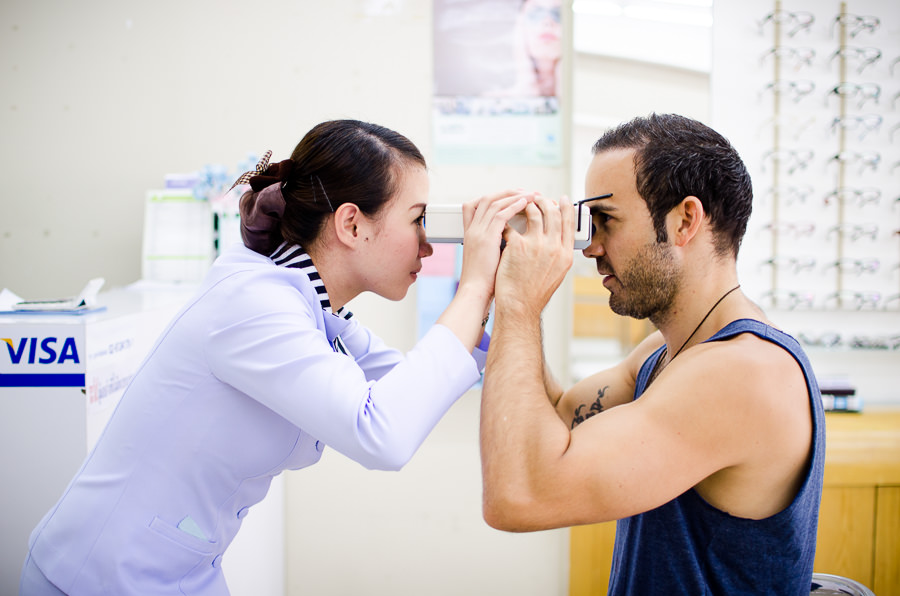 Adrian getting his eyes tested by a woman in Chiang Mai, Thailand.
