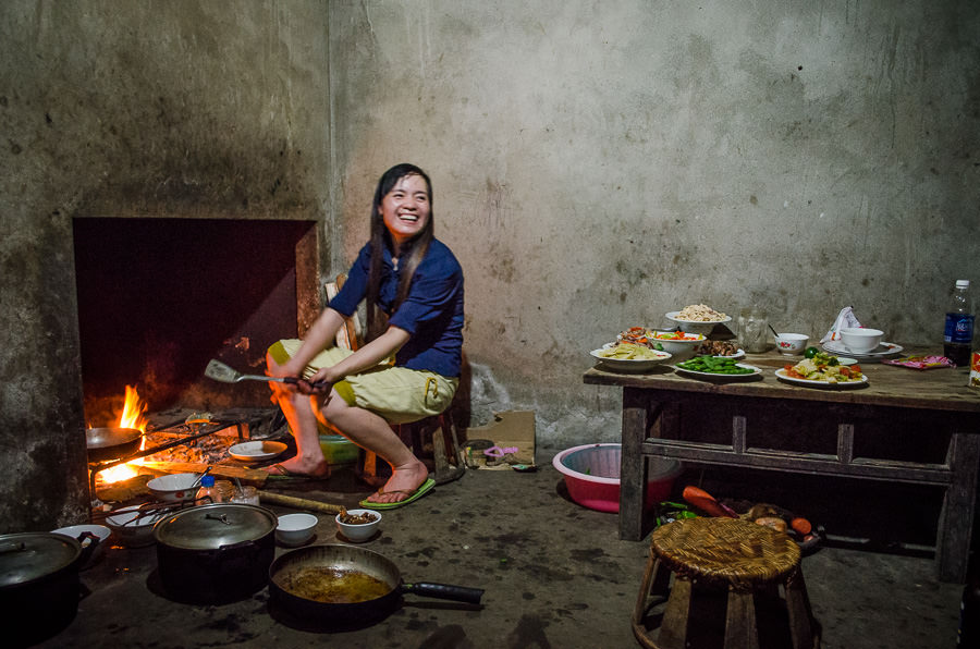 Woman cooking in the kitchen of a homestay in Ta Van Village, Vietnam. Dangers Vietnam include theft like happened at this homestay.