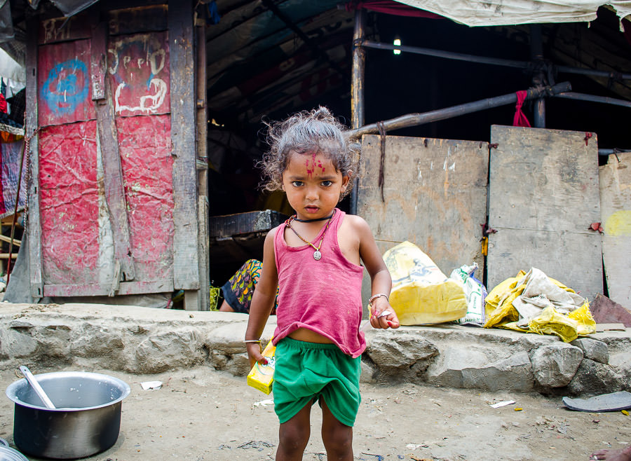 Young girl standing outside of her tent home in Kathmandu, Nepal.