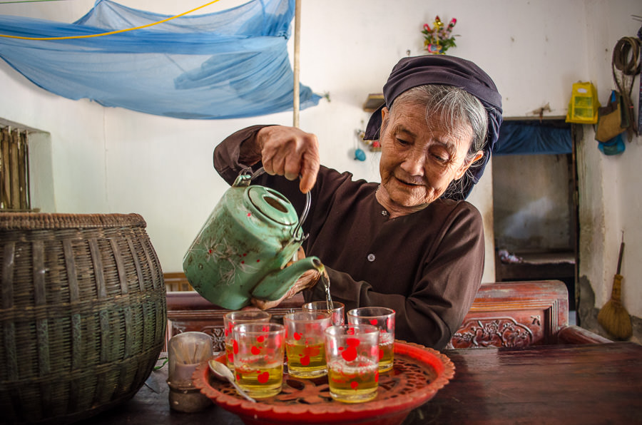 Old woman pouring tea