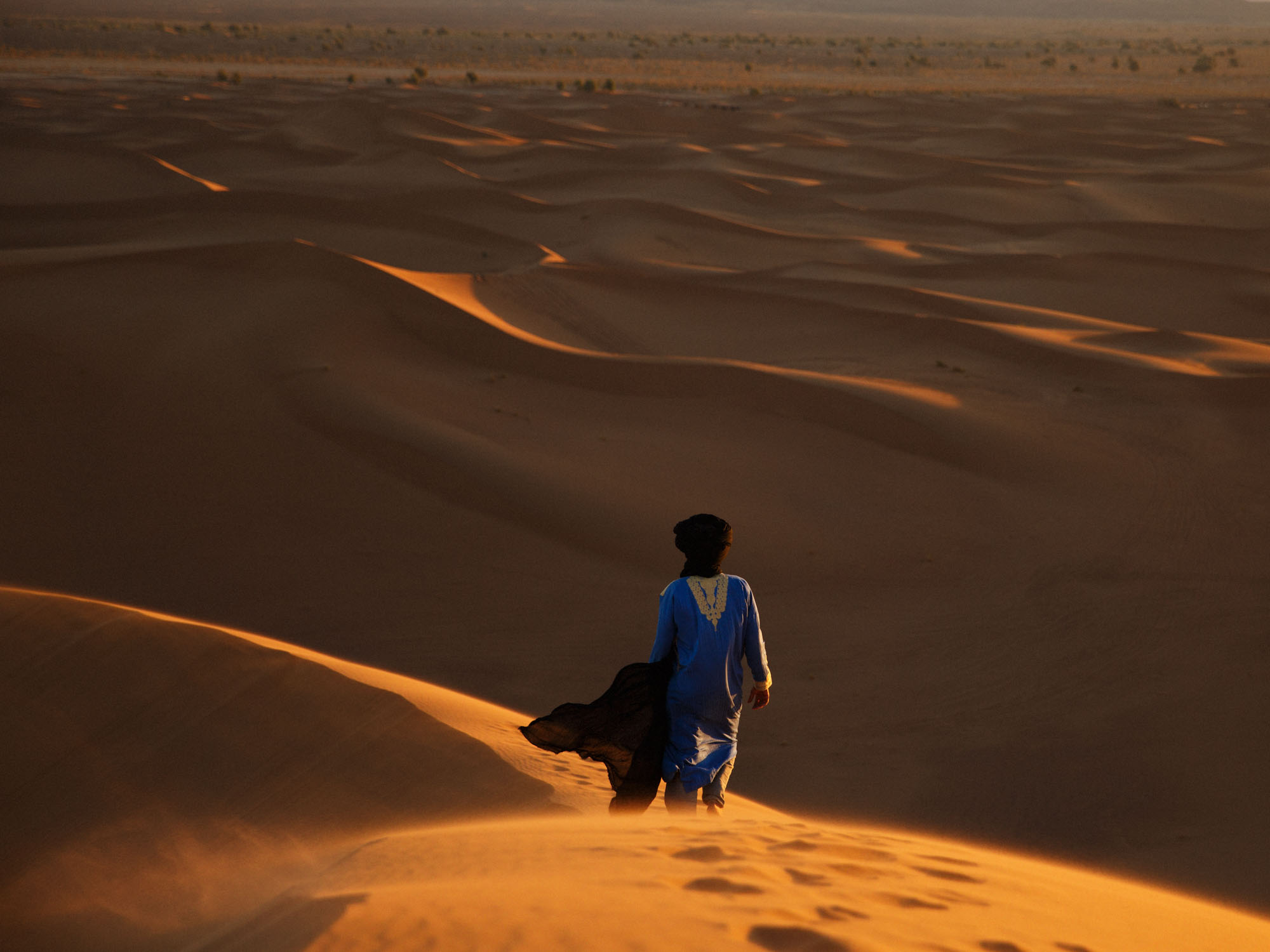 Beldi Nomad Walking Accross Moroccan Sahara Sand Dunes
