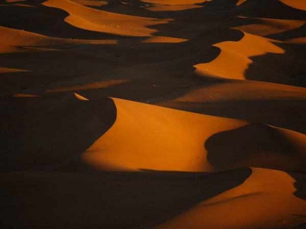 Orange Moroccan Desert Sand Dunes Casting Shadows under the Moonlight