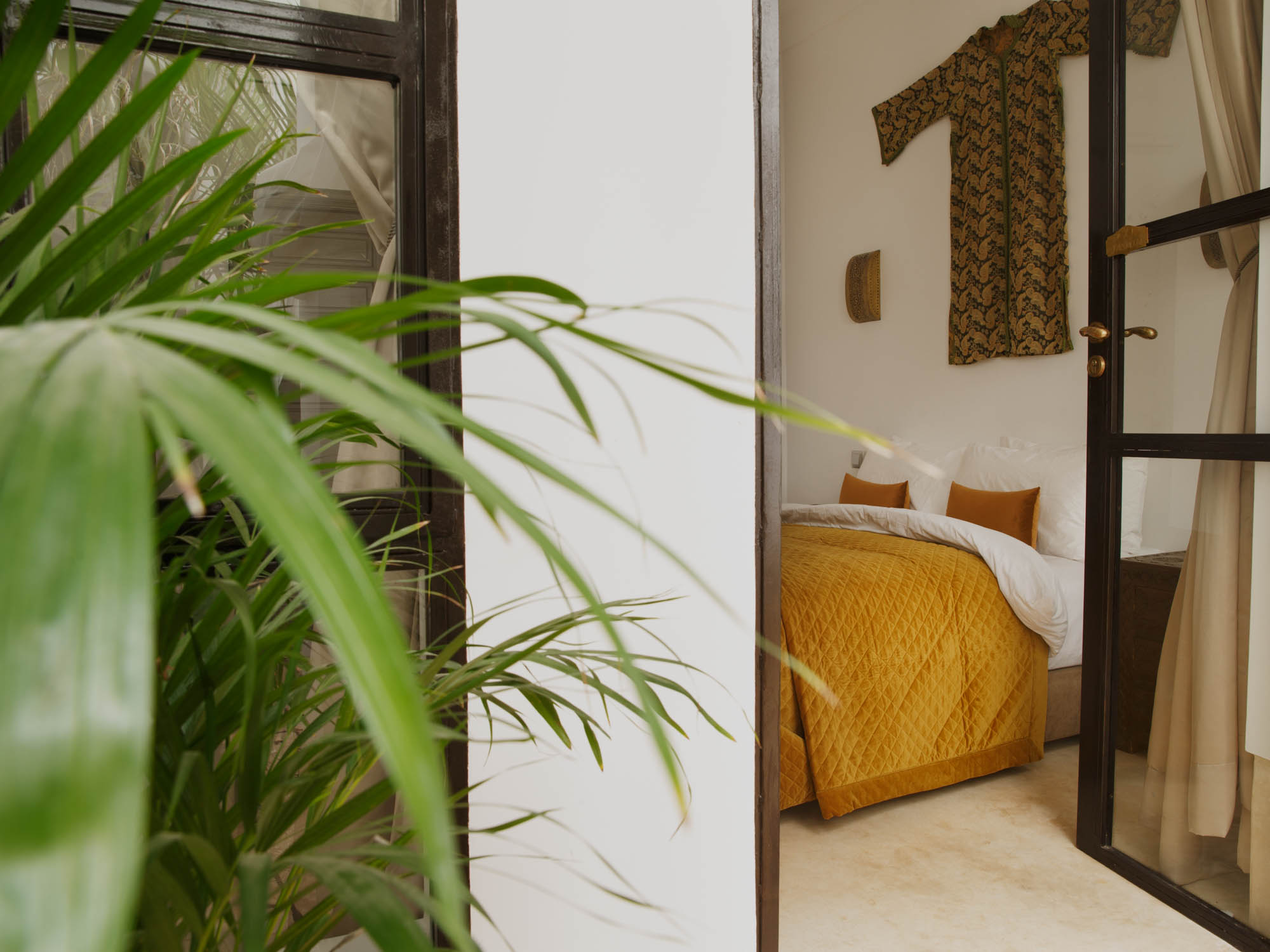 Luxury Bed in Bedroom at Riad hotel with Door Leading to Patio with Broad leaf potted plants