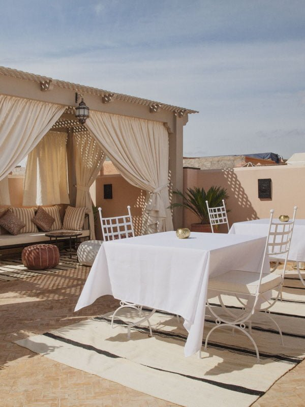 Dining Table on Rooftop Terrace Outside Hotel Room With Couch and Moroccan Leather Poufs